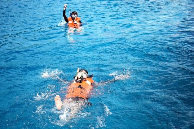 Persone che fanno snorkeling in acque tropicali. immersioni, snorkeling e vedere i pesci.