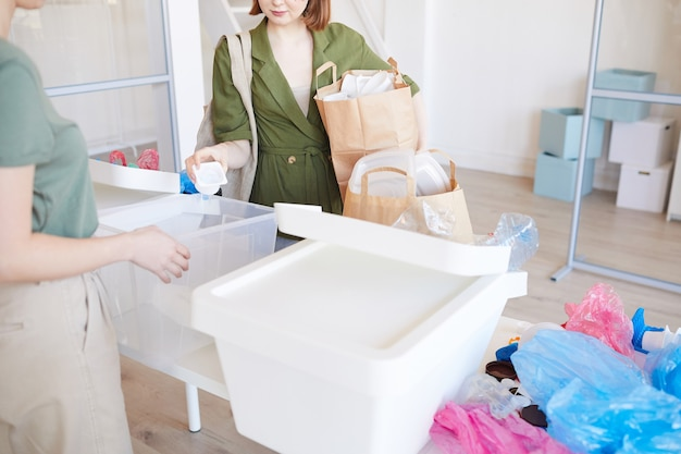 Persone che smistano plastica a casa, concentrarsi sulla donna che tiene i sacchetti di carta con oggetti pronti per il riciclaggio