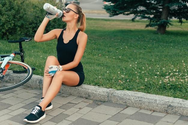 Persone, sport, 4k, emozioni, concetto naturale e lifestyle - ritratto di ragazza abbastanza carina sorridente accanto al suo parco bici con palme in una giornata di sole. ciclista donna che beve acqua durante l'allenamento in bicicletta