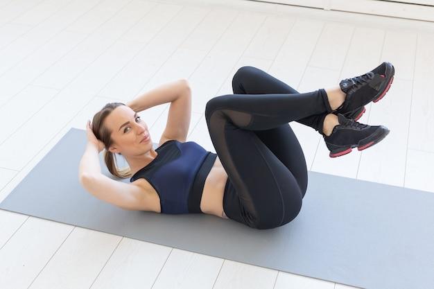 Concetto di persone, sport e fitness - giovane donna fitness facendo esercizio di crunch addominali sul pavimento a casa