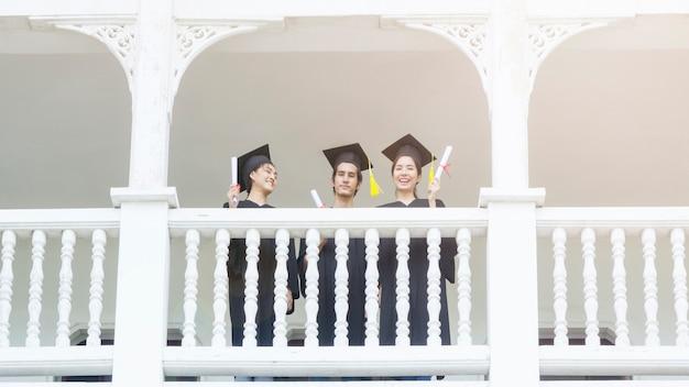 Studenti della gente con gli abiti di laurea