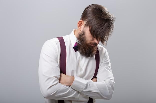 Persone, stile e concetto di moda - ritratto di uomo barbuto vestito con una camicia bianca sul muro grigio.