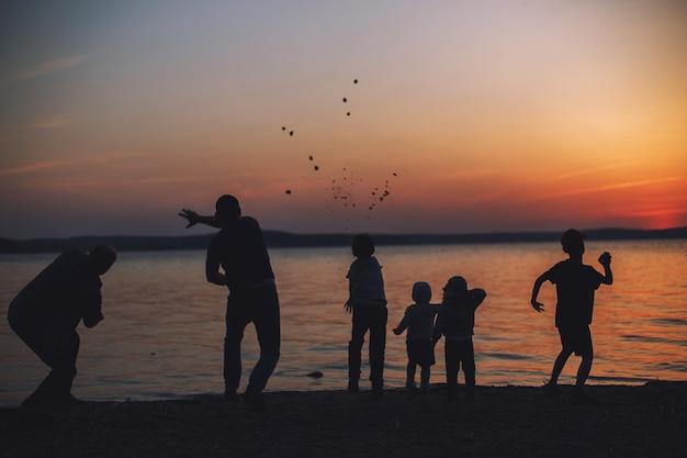 Persone al tramonto che lanciano pietre nell'acqua