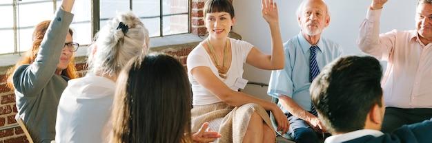 Persone in un gruppo di supporto che alzano la mano