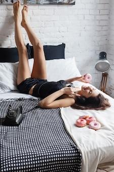 Persone, dolci e concetto di fast food - giovane donna o ragazza felice che mangia ciambella, inginocchiata a letto. la bella ragazza sexy esile sta trovandosi a letto con le ciambelle dolci, l'ora della colazione, il concetto di buongiorno