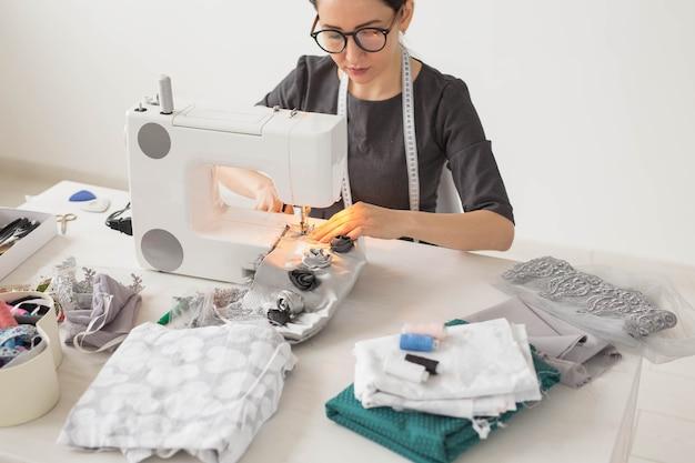 Persone, sarto e concetto di moda - close up ritratto di designer di moda posto di lavoro con macchina da cucire