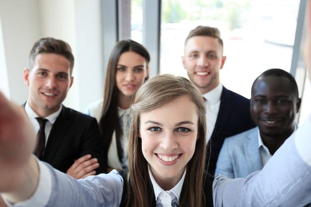Persone che si fanno selfie durante una riunione di lavoro