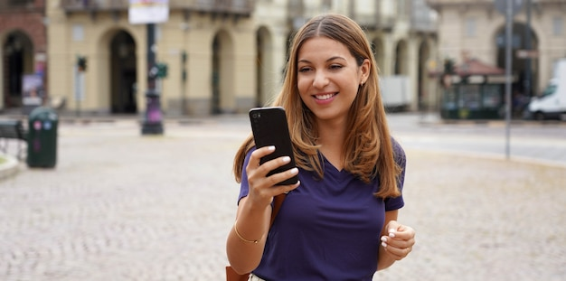 Persone e tecnologia. banner panoramico di una studentessa sorridente allegra che cammina sullo sfondo della città vecchio stile in una giornata nuvolosa.
