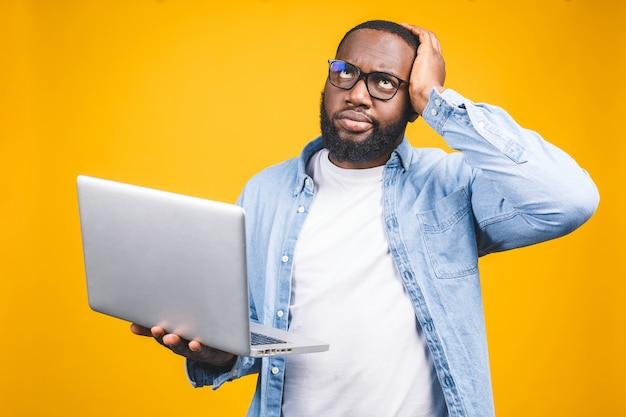 Concetto di persone e stanchezza. l'uomo nero afroamericano affaticato si toglie gli occhiali, si sente assonnato e oberato di lavoro, circondato da tecnologie moderne.