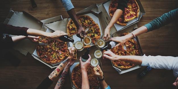 Le persone insieme mangiano pizza e bevono birra