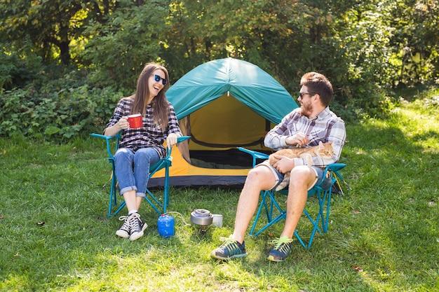 Concetto di persone, turismo e natura - coppie che si divertono in campeggio e giocano con il gatto