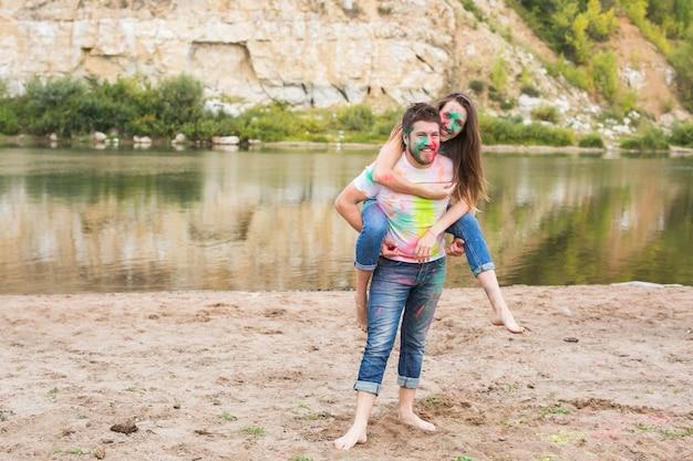Concetto di persone, turismo e natura - coppia sorridente con facce dipinte che si divertono.