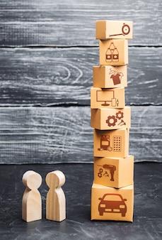 Persone e una torre di scatole di cartone con merci acquisto e vendita di beni servizi relazioni commerciali la crisi economica e le nuove tendenze
