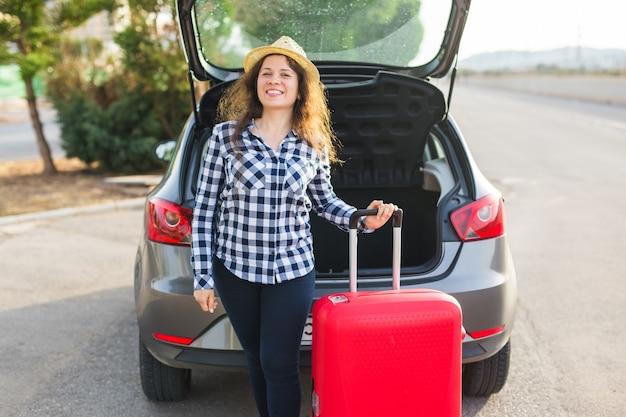 Persone, trasporto e concetto di viaggio: la donna allegra è in piedi vicino alla sua auto e si sta chiudendo