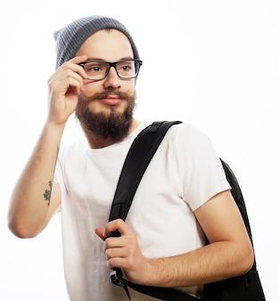Concetto di persone, viaggi, turismo e istruzione - felice giovane uomo barbuto in occhiali che indossa un cappello, con zaino su sfondo bianco