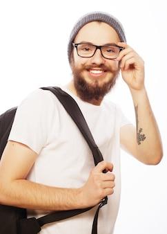 Concetto di persone, viaggi, turismo e istruzione. felice giovane uomo barbuto in occhiali che indossa il cappello, con zaino su bianco
