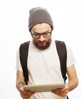 Concetto di persone, viaggi, turismo e tecnologia - felice giovane uomo barbuto in occhiali con zaino e tablet su superficie bianca