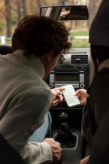 Persone che viaggiano insieme in macchina e controllano una nuova destinazione