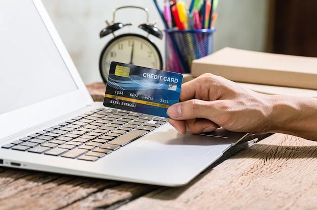 Le persone usano le carte di credito per fare acquisti online tramite computer notebook.