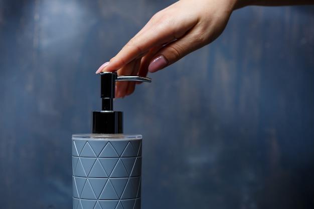 Le persone usano il distributore di sapone con un cappuccio di metallo grigio su un tavolo grigio