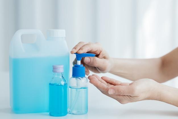 Le persone che usano una bottiglia di disinfettante antibatterico con gel in alcool