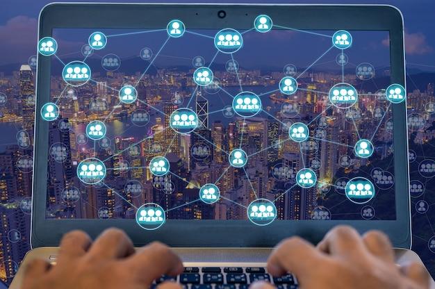 Le persone che usano il laptop per connettersi con un'altra persona con il diagramma di rete wireless sul paesaggio urbano di notte che rappresentano la comunicazione internet in worldwild.