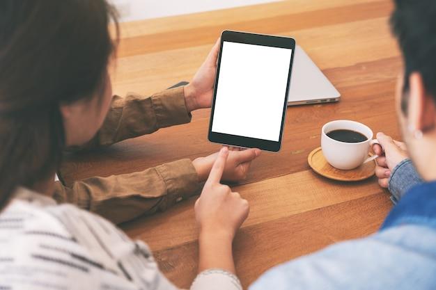 Persone che usano, guardano e puntano insieme allo stesso tablet pc mockup su un tavolo di legno