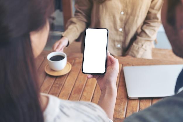Persone che usano e guardano insieme lo stesso telefono cellulare mockup su un tavolo di legno