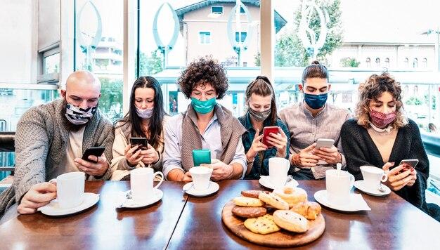 Persone che utilizzano telefoni cellulari intelligenti al bar coperto da maschere facciali