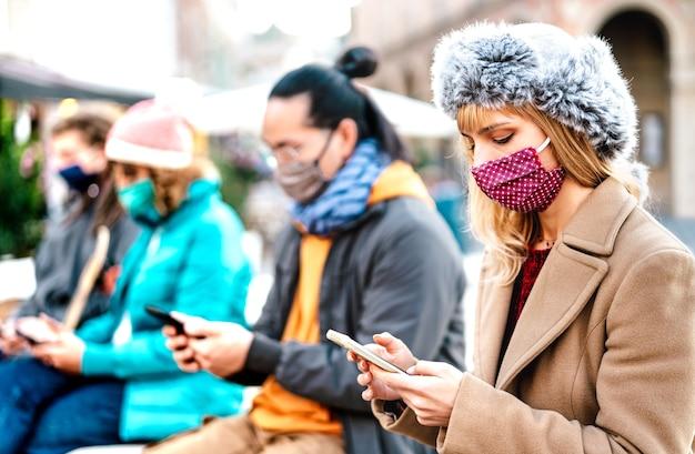 Persone che utilizzano smartphone coperti da maschera durante la seconda ondata di covid