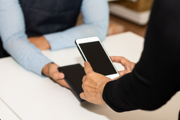 Le persone che utilizzano lo smartphone mobile banking scansionano il codice qr per pagare in negozio