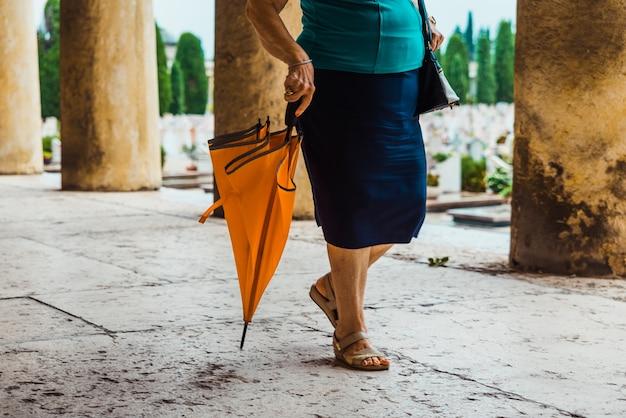 La gente cammina con gli ombrelli in un giorno di pioggia attraverso un cimitero.