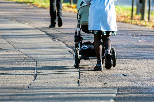 Persone che camminano sul marciapiede asfalto in giornata di sole, gambe di donna e passeggino con il primo piano ombra