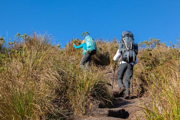 La gente che cammina con grandi zaini nel paesaggio montano - trekking escursionismo mountaneering in mantiqueira gamma brasile