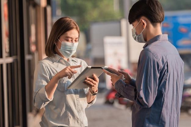 Le persone indossano una maschera facciale per proteggere il coronavirus parlando di affari con la tecnologia dei tablet