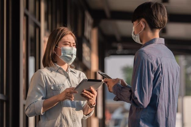 Le persone indossano una maschera facciale per proteggere il coronavirus parlando di affari con la tecnologia tablet