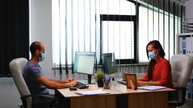 Persone che indossano maschere per il viso e puliscono l'igienizzazione delle mani con gel alcolico prima di iniziare a lavorare al computer. nuova normale misura di allontanamento sociale e stile di vita lavorativo sulla crisi del virus corona.