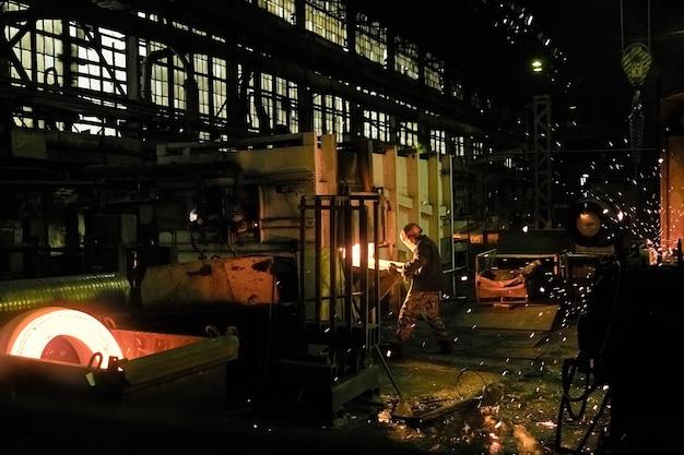 Persone che saldano il metallo durante il lavoro nell'impianto di lavorazione dei metalli