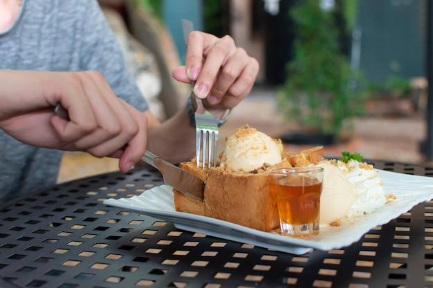 Le persone usavano le mani per tagliare il pane tostato al miele con una broccia e un coltello in acciaio inossidabile posto in un piatto con gelato, miele e panna montata.
