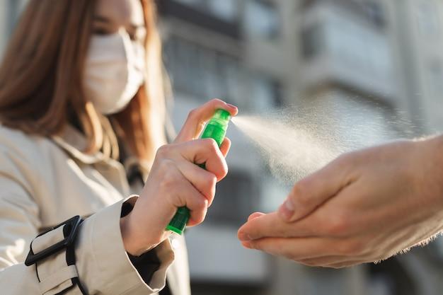 Le persone che usano gel antisettico a base alcolica e indossano una maschera preventiva prevengono l'infezione con l'epidemia di coronavirus covid-19, una donna si lava le mani di un uomo con un disinfettante per le mani