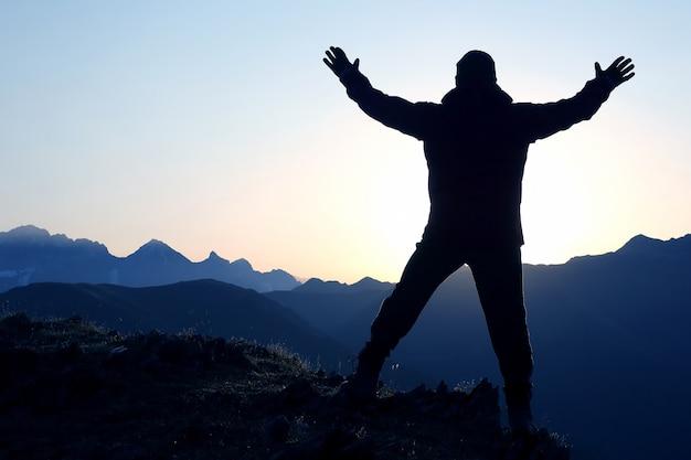 Persone con le braccia alzate in piedi sulla montagna all'alba