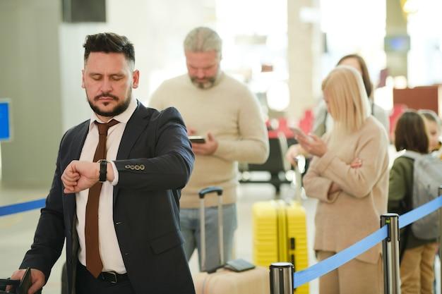 Persone con bagagli in coda per il check-in in aeroporto