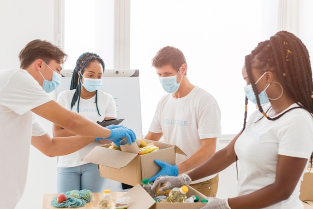 Persone con maschere mediche che preparano pacchetti di donazioni