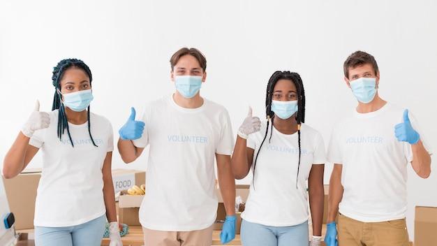 Persone con maschere mediche che fanno volontariato
