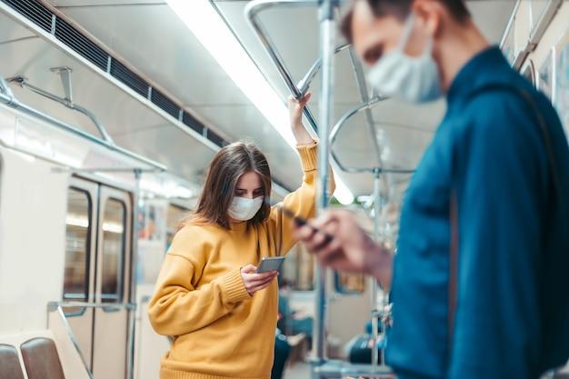 Persone con smartphone in piedi in un vagone della metropolitana. coronavirus in città