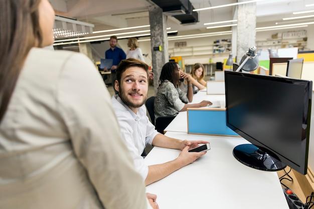 Persone che lavorano in un ufficio moderno occupato davanti ai computer