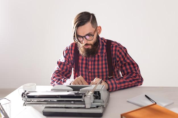 Concetto di persone, scrittore e hipster - giovane scrittore alla moda che lavora alla macchina da scrivere
