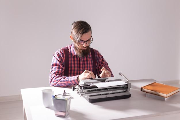 Concetto di persone, scrittore e hipster - giovane scrittore alla moda che lavora alla macchina da scrivere.