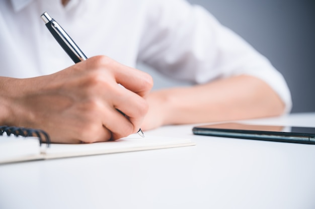 Persone che scrivono sul taccuino e lavorano con la carta sul tavolo di legno.