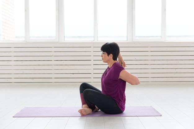 Persone, yoga, sport e concetto di assistenza sanitaria - donna attraente che allunga le mani in alto che si siede sullo yoga